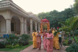 Monks carry the palanquin around ashram grounds.