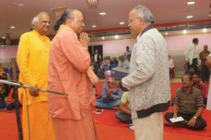 Swamiji presents Guruji's books to a senior editor of local newspaper.