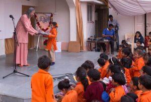 Swami Vasudevananda distributes gifts to all participants.