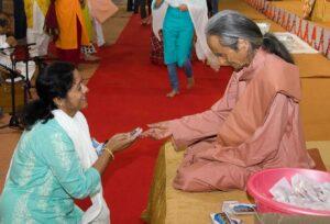 Swami Nirvanananda distributes prasad.