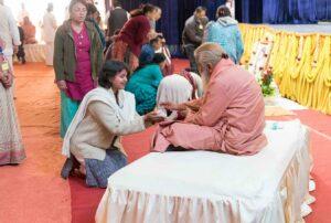 Swamiji distributes prasad.