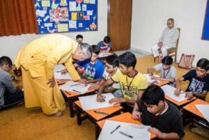 Brahmachari Vinayananda assists a boy in his 3D drawing.