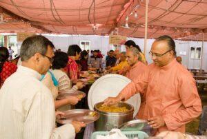 Monks serve prasad after the diksha ceremony.
