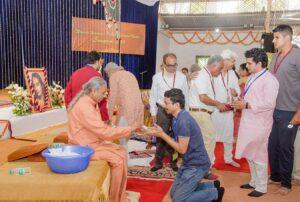 Devotees come forward for pranaming and prasad.