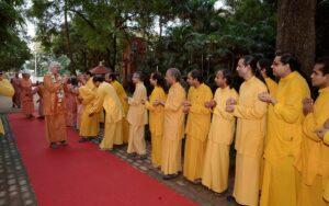 Monks shower flowers at Swamiji's feet as he pranams.