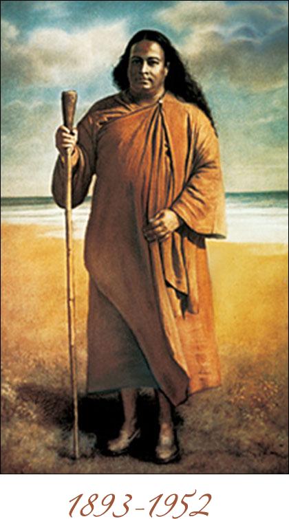 Paramahansa Yogananda standing on a seashore with his stick
