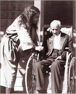 Paramahansa Yogananda with a man on a wheelchair.